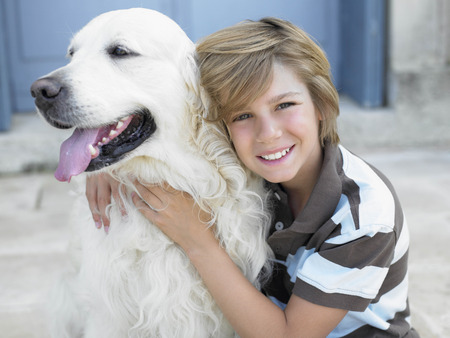 Boy smiling,  with dog on door step