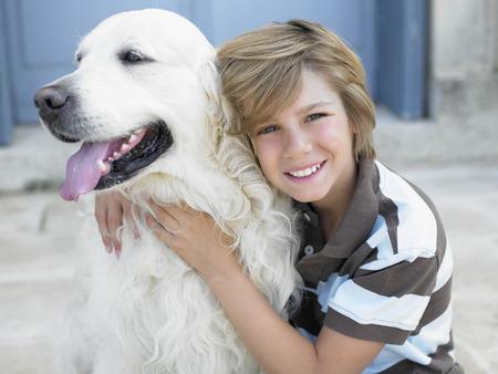 Junge, der, mit Hund auf Türschritt lächelt