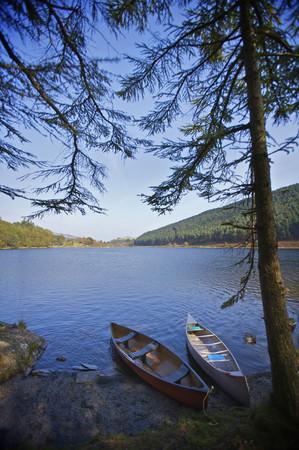 Two kayaks on a lake side.