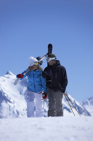 scaling: Couple walking with skis over shoulder LANG_EVOIMAGES