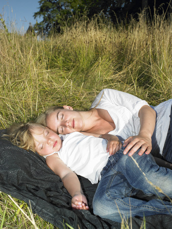 Mother and daughter sleeping in a field LANG_EVOIMAGES