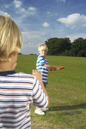 equivalents: boy throwing frisbee to another boy