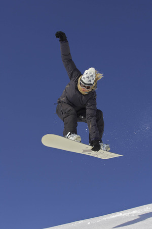 Female snowboarder jumping with a grab