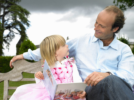 hombre sentado: Father and daughter reading a book