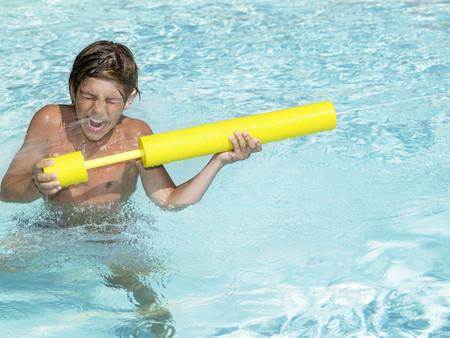 rejuvenated: Boy playing with water gun in pool