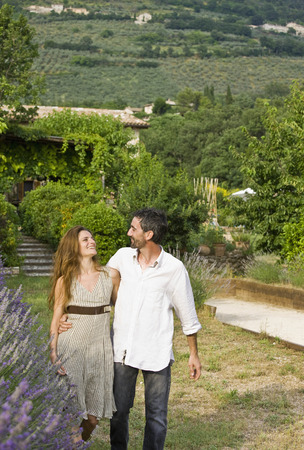 passions: Portrait of couple walking in garden