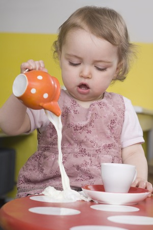 sipping: Young girl spilling milk on table