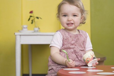 tempted: Young girl on table with sundae