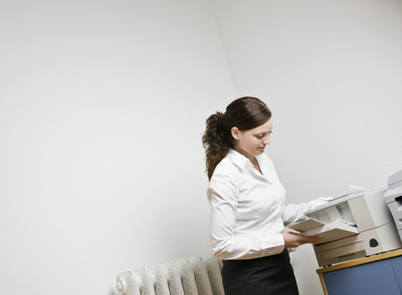 Woman filling a printer with paper LANG_EVOIMAGES