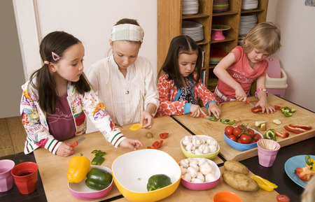 worktops: Four girls cutting vegetables LANG_EVOIMAGES