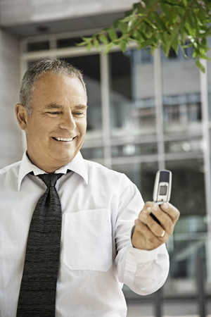 responding: Man with his cellular phone, smiling