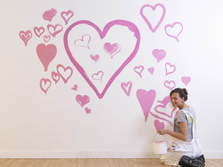 enthusiastically: Girl paints pink hearts. LANG_EVOIMAGES
