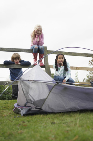 leaning by barrier: Children with tent