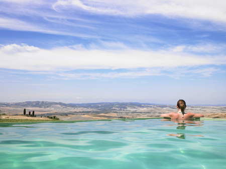 Woman in pool admiring view LANG_EVOIMAGES