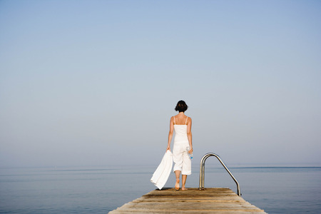 Woman walking on a pier LANG_EVOIMAGES