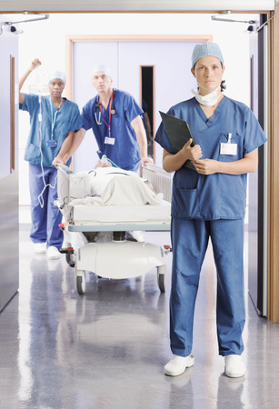 rushed: Three doctors pushing a patient in bed