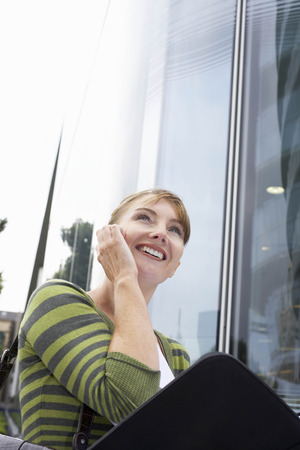 reviews: Business woman using mobile outside