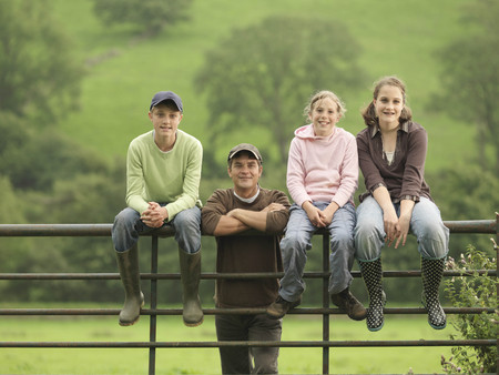 leaning by barrier: Farmer With Children On Gate
