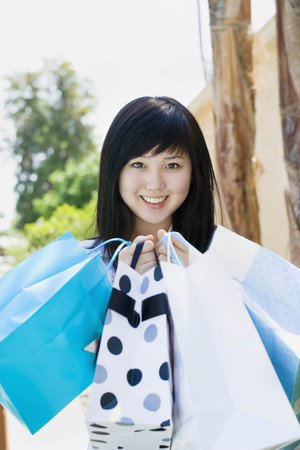 commodities: Adolescente sonriente con bolsas de compras LANG_EVOIMAGES