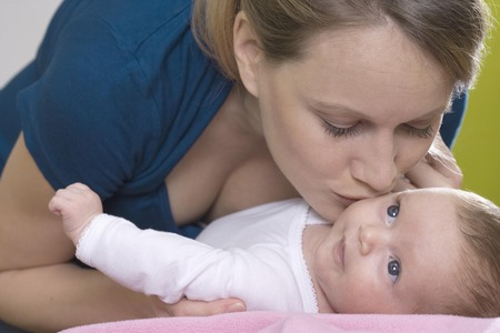 lays down: Young mother kissing her baby