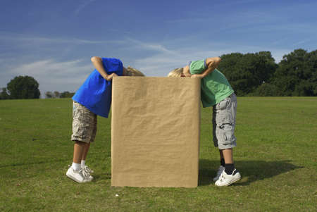 equivalents: two boys looking into box LANG_EVOIMAGES