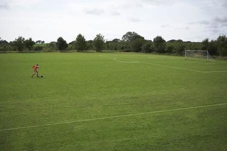 rehearse: Footballer dribbling a ball towards goal