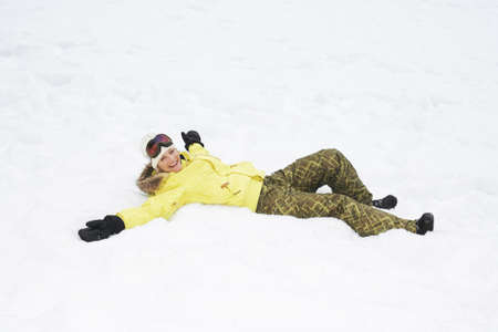 snows: Girl in yellow jacket lying in snow