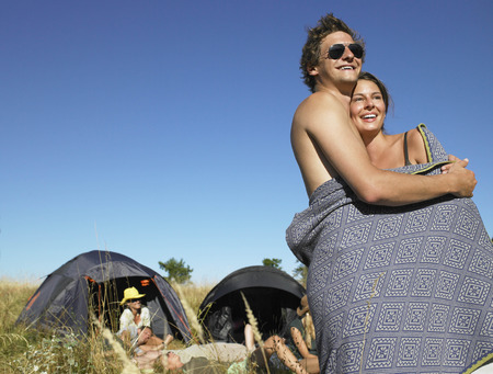 Couple wrapped in a cover at a festival LANG_EVOIMAGES