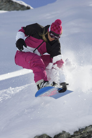 exhilarating: Female snowboarder jumping with a grab