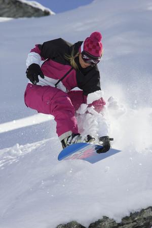 agachado: Mujer snowboarder saltando con un agarre