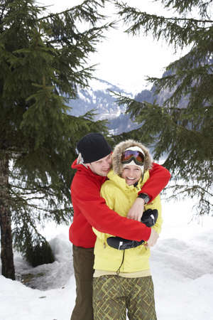 Laughing couple in love,  snow wear LANG_EVOIMAGES