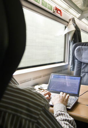 accomplishes: Man typing on laptop on train