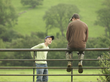 Farmer Talking To Son On Gate