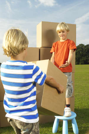 equivalents: boy handing box to his brother LANG_EVOIMAGES