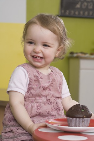 tempted: Young girl on table with muffin