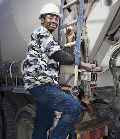 scaling ladder: Construction worker on cement mixer LANG_EVOIMAGES