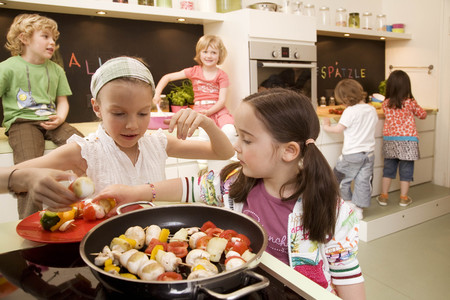 medium body: Girls and boys cooking vegetables