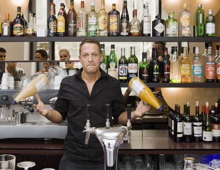 tosses: Portrait of bartender spinning drinks