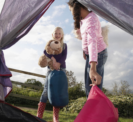 adventuresome: Girls putting sleeping bags in tent LANG_EVOIMAGES