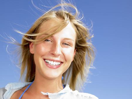 Woman smiling,  blue sky above LANG_EVOIMAGES