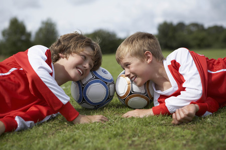 level playing field: Two boys laughing with heads on balls LANG_EVOIMAGES