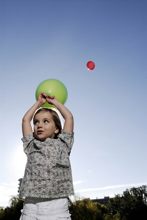 5 years old girl holding a balloon LANG_EVOIMAGES