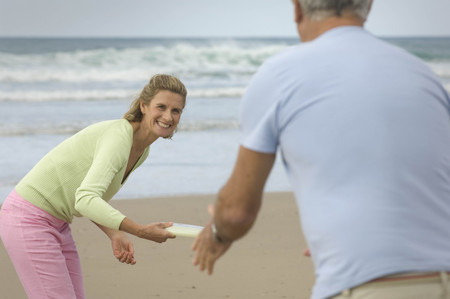 flying disc: Couple playing frisbee on a beach