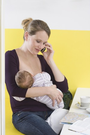 Mother breastfeeding baby,  on the phone LANG_EVOIMAGES