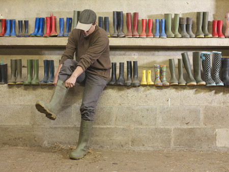 dirtied: Farmer Putting On Wellington Boots