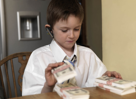 handsfree telephones: Boy counting money at table LANG_EVOIMAGES