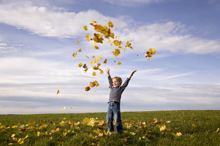 Boy throwing leaves into the air