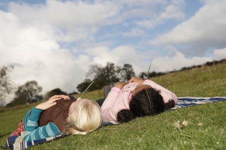 lays down: Two girls lying on hillside