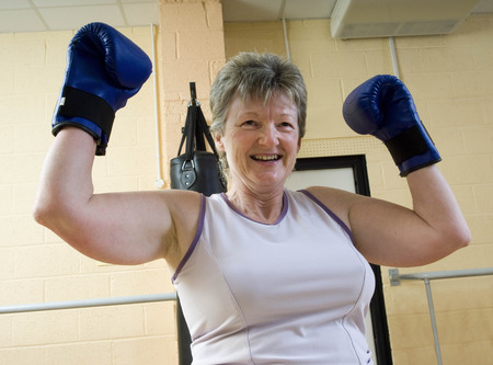 enthusiastically: woman winning at boxing exercise at gym