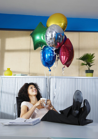 Young woman with balloons in office LANG_EVOIMAGES